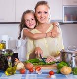 Maman et petite fille faisant cuire le plat vegeterian à l'intérieur Image libre de droits