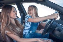 Maman et sa fille conduisant une voiture photographie stock libre de droits