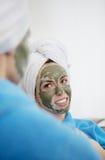 Maman et sa fille refroidissant dans la chambre à coucher et faisant le masque de massage facial d'argile Images stock