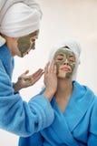 Maman et sa fille refroidissant dans la chambre à coucher et faisant le masque de massage facial d'argile Photographie stock