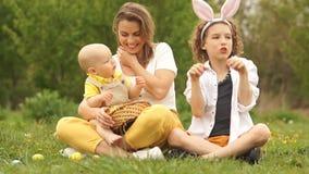 Maman et ses deux fils dans le pré Pique-nique de Pâques, costume de lapin Famille heureuse de P?ques banque de vidéos
