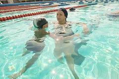 Maman et son fils dans la piscine Donner de mère photos libres de droits