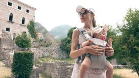 Maman et son voyage de bébé avec le sac à dos de transporteur de bébé des vacances d'été images stock