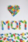 MAMAN et un coeur avec les blocs en bois colorés de jouet Images stock
