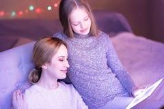 Maman exubérante et fille regardant l'ordinateur portable et étreindre Photographie stock