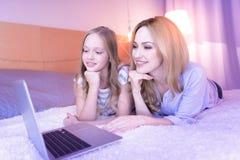 Maman exubérante et fille regardant l'ordinateur portable Photos libres de droits