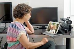 Maman faisant un appel éloigné sur l'Internet photo stock