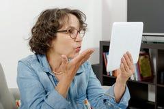 Maman faisant un appel éloigné sur l'Internet Photos stock