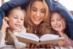 Maman gaie lisant un livre pour ses filles Photographie stock libre de droits