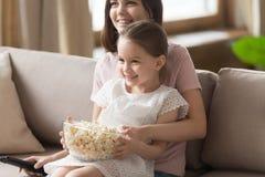 Maman heureuse de famille avec la fille mignonne d'enfant regardant la TV ensemble images stock