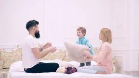 Maman heureuse de famille, papa et peu de fils ayant le combat d'oreiller d'amusement sur le lit, jeune mère, joie riante de sens clips vidéos