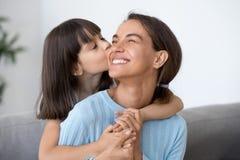 Maman heureuse de petit baiser mignon de fille sur la joue image stock