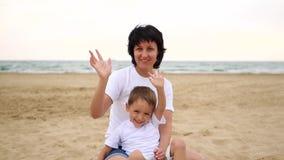 Maman heureuse et bébé s'asseyant sur une plage de mer ondulant et souriant, dans le mouvement lent banque de vidéos