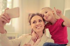 Maman heureuse et fille positives prenant des selfies ensemble photo stock