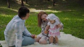 Maman heureuse et papa de famille jouant avec le bébé sur le couvre-lit banque de vidéos