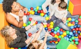 Maman heureuse et papa multiraciaux jouant avec la fille au gameroom Image stock