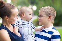 Maman heureuse et ses enfants jouant en parc ensemble Photo stock