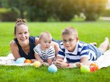 Maman heureuse et ses enfants jouant en parc ensemble Photos stock