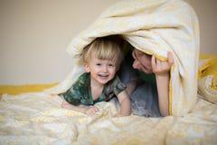 Maman heureuse jouant avec son fils dans le lit par matin décontracté Images libres de droits