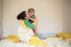 Maman heureuse jouant avec son fils dans le lit par matin décontracté Photo libre de droits
