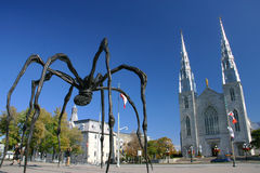 "Maman by Louise Bourgeois and the Notre Dame Cathe. A giant bronze sculpture of spider called ""Maman"" by Louise Bourgeois standing at the main entrance the Royalty Free Stock Image"