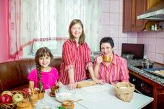 Maman lui enseignant deux filles faisant cuire sur la cuisine Image stock