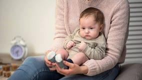 Maman massant les pieds de bébés, méthode pour calmer nouveau-né tatillon, prévention de pied plat images stock
