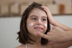 Mère appliquant la protection solaire Image libre de droits