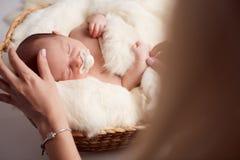 Maman mettant le bébé pour dormir dans le lit de bébé à la maison Photographie stock