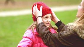 Maman mettant le chapeau sur la tête de la fille et l'embrassant dans le front clips vidéos