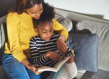 Maman noire apprenant la fille pour lire images stock