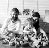 Maman, papa et enfant avec des jouets sur la construction en bois de fond hors des blocs Amour et concept de jeux de famille La j Images libres de droits