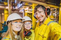 Maman, papa et fils dans un uniforme jaune, les verres, et le casque de travail dans un milieu industriel, plateforme pétrolière  image libre de droits