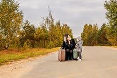 Maman parlant avec son petit fils s'accroupissant avec de rétros valises photos stock