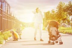 Maman parlant par le téléphone pendant la promenade extérieure avec des enfants Photographie stock libre de droits