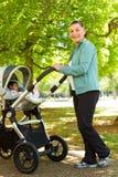 Maman poussant son bébé dans une poussette photo libre de droits