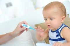 Maman prenant la température en difficulté de childs Image libre de droits