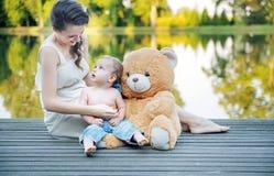 Maman regardant son garçon jouant l'ours de nounours Image libre de droits