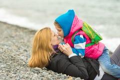 Maman s'asseyant sur la plage sur un frais qui montre la distance à une fille s'asseyant sur ses mains Photo libre de droits
