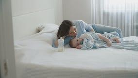 Maman se couchant à côté de son petit fils et ayant un repos banque de vidéos