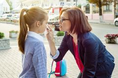 Maman soulageant son écolière pleurante de fille sur le chemin de la maison d'école Photographie stock libre de droits