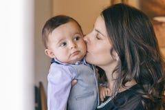 Maman tenant et embrassant son bébé garçon avec affection Photo stock