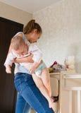 Maman tenant le bébé La maman nettoie des vêtements de bébé Photo stock