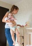 Maman tenant le bébé La maman nettoie des vêtements de bébé Photos stock