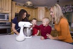 Mamans enseignant des gosses à faire cuire au four Image libre de droits