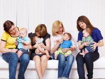 Mamas que toman el cuidado de sus niños Imagenes de archivo