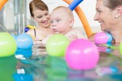 Mamas und Babys, die Spaß am Säuglingsschwimmwettbewerb haben Lizenzfreies Stockbild