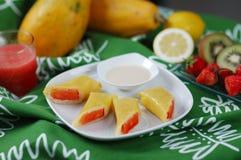 Mamgo papaya rollers. Fresh health mango papaya rollers on table Stock Photography