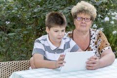 Mamie avec le comprimé de observation de petit-fils en nature Images libres de droits