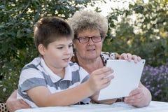 Mamie avec le comprimé de observation de petit-fils en nature Photo libre de droits